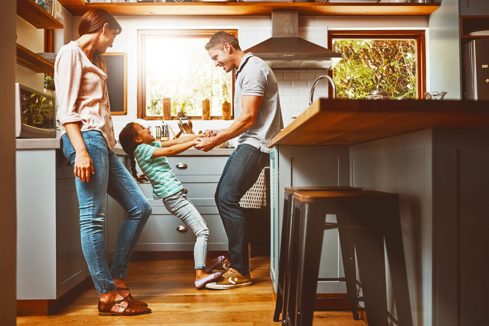 Parents and child playing in kitchen